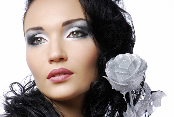 Beautiful woman with silver rose looking away...
