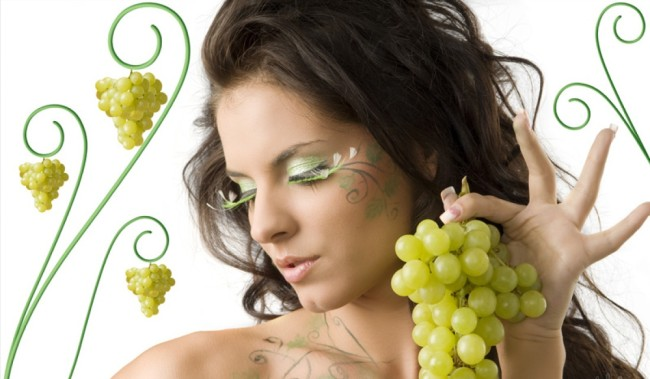 pretty girl with bodypaint on shoulder and face looking down with grape